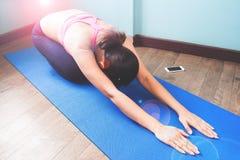 Femme active faisant le yoga sur le tapis bleu de yoga, établissant Image libre de droits