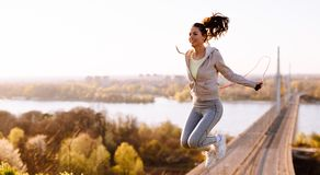 Femme active sautant avec la corde à sauter dehors photos libres de droits