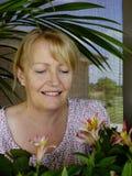 Femme admirant de nouvelles fleurs Photo stock