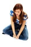 Femme adolescente fâchée s'asseyant sur le plancher et criant Photo libre de droits