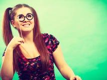 Femme adolescente heureuse tenant de fausses lunettes sur le bâton photographie stock
