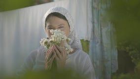 Femme adorable avec le châle blanc sur ses marguerites de reniflement de tête regardant la caméra près de la corde à linge dehors clips vidéos
