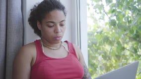 Femme adorable d'Afro-américain de portrait jeune s'asseyant sur le filon-couche de fenêtre dactylographiant sur son ordinateur p clips vidéos