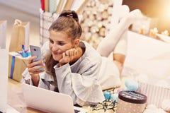 Femme adulte à la maison enveloppant des cadeaux de Noël photo libre de droits