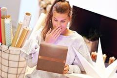 Femme adulte à la maison enveloppant des cadeaux de Noël images libres de droits