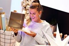 Femme adulte à la maison enveloppant des cadeaux de Noël photographie stock