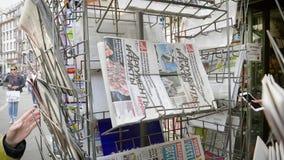 Femme adulte achetant les journaux internationaux au kiosque de presse banque de vidéos