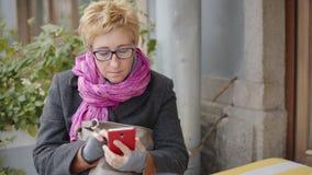 Femme adulte avec du café et le smartphone banque de vidéos