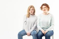 Femme adulte avec l'adolescente s'asseyant l'un à côté de l'autre images stock