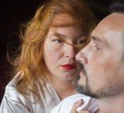 Femme adulte avec l'ivrogne rouge de cheveux avec un légers sourire et regard dans l'amour regardant son homme Photographie stock libre de droits