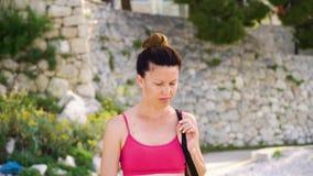 Femme adulte avec le petit pain de cheveux dans les vêtements de sport marchant dehors en soleil de matin clips vidéos