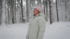 Femme adulte avec les cheveux blonds, qui sont cachés sous le chapeau rose, utilisant une veste blanche d'hiver, se tenant au mil banque de vidéos