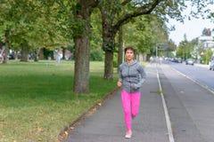 Femme adulte convenable courant sur un trottoir photo libre de droits