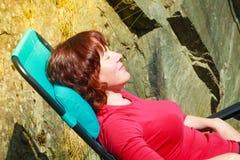 Femme adulte détendant sur le lit pliant dans le jardin photographie stock libre de droits