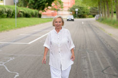 Femme adulte dans toute la marche blanche à la rue Image stock