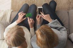 Femme adulte et fille employant la vue supérieure de smartphone Photographie stock libre de droits