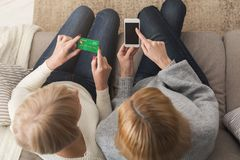 Femme adulte et fille employant la vue supérieure de smartphone Image libre de droits