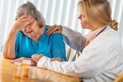 Femme adulte féminine de docteur Consoling Distraught Senior photos stock
