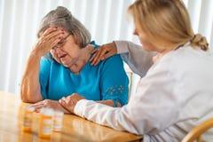 Femme adulte f?minine de docteur Consoling Distraught Senior images stock