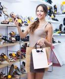 Femme adulte gaie se tenant avec la chaussure choisie Images stock