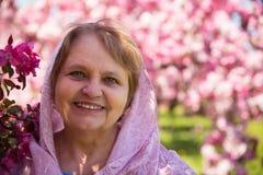Femme adulte heureuse dans le foulard sous la fleur pourpre Photographie stock libre de droits