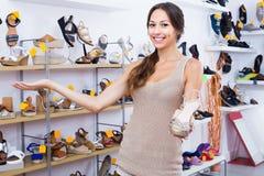 Femme adulte heureuse se tenant avec la chaussure choisie Photographie stock libre de droits