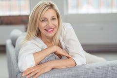 Femme adulte heureuse sur le divan regardant l'appareil-photo Photo stock