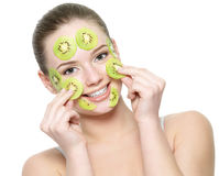 Femme adulte heureux avec le masque de massage facial de kiwi Image stock