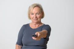 Femme adulte jugeant à télécommande contre le gris Image libre de droits