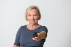 Femme adulte jugeant à télécommande contre le gris Images stock