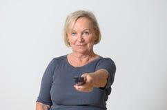 Femme adulte jugeant à télécommande contre le gris Images libres de droits