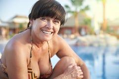 Femme adulte prenant un bain de soleil par la piscine photographie stock