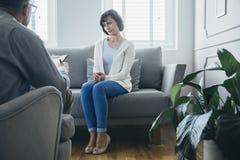 Femme adulte résolvant ses problèmes avec le psychothérapeute images stock