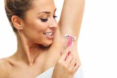 Femme adulte rasant l'aisselle avec le rasoir rose d'isolement sur le fond blanc photo stock