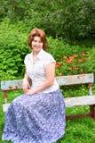 Femme adulte s'asseyant sur un banc dans le jardin Photo stock