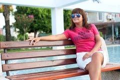 Femme adulte s'asseyant sur un banc en parc photos stock