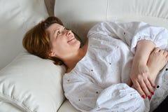Femme adulte se trouvant sur le sofa Photos stock