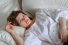 Femme adulte se trouvant sur le sofa Photo libre de droits
