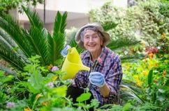 Femme adulte supérieure positive posant avec la boîte d'arrosage dans le jardin photos libres de droits