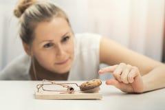 Femme affamée essayant de voler le biscuit du piège de souris Photographie stock