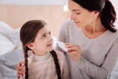 Femme affectueuse donnant des gouttes pour le nez à un enfant de sourire Images stock