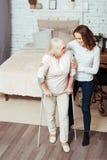 Femme affectueuse positive aidant mamie handicapée à marcher avec des béquilles Photos stock