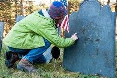 Femme affichant la vieille pierre tombale avec l'indicateur Image stock