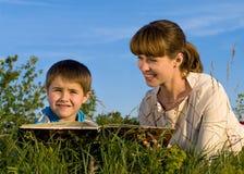 Femme, affichant un livre au jeune garçon Photographie stock