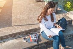 Femme affichant un livre en stationnement images stock