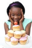 Femme africain étonné regardant des gâteaux images stock
