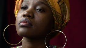 femme africaine aux yeux noirs avec des boucles d'oreille d'or posant dans des vêtements nationaux, mouvement lent banque de vidéos