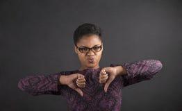 Femme africaine avec de pouces le signal de main vers le bas sur le fond de tableau noir Photo libre de droits