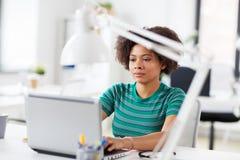 Femme africaine avec l'ordinateur portable au bureau Images libres de droits