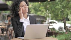 Femme africaine avec le mal de tête utilisant l'ordinateur portable en café extérieur banque de vidéos